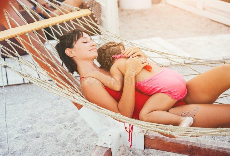Madre felice con sua figlia che si trova in un'amaca fotografia stock libera da diritti
