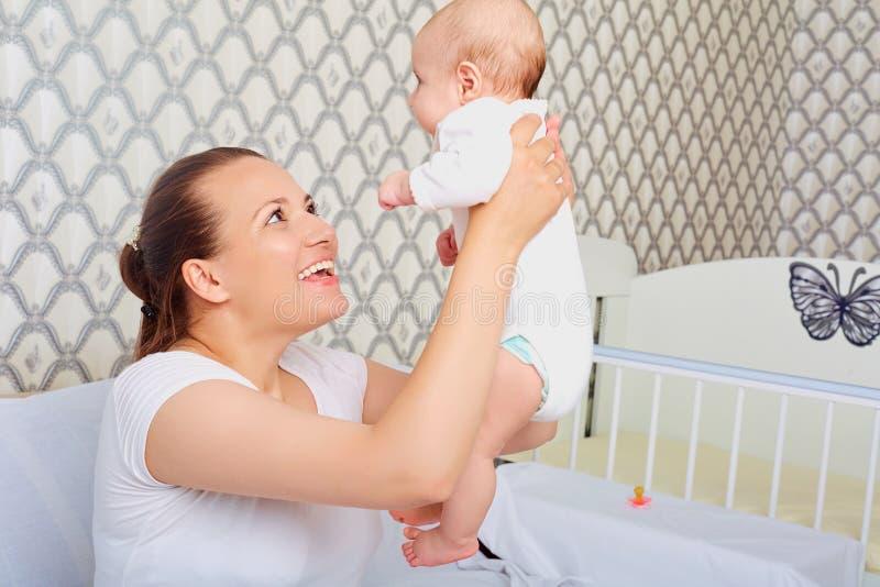 Madre felice con un bambino in lei armi Su Mamma con il bambino immagini stock
