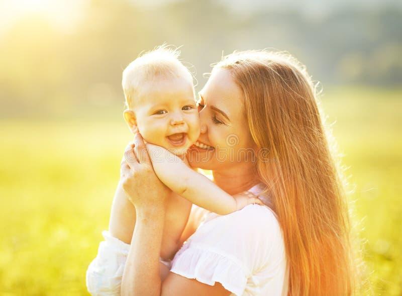 Madre felice della famiglia ed abbracciare e bacio del bambino di estate su natur immagine stock