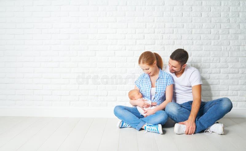 Madre felice della famiglia, padre di un neonato sul pavimento vicino a blan immagine stock libera da diritti