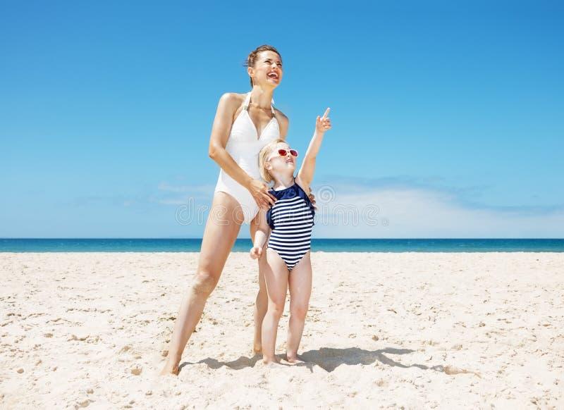 Madre felice e bambino che indicano da qualche parte alla spiaggia sabbiosa fotografie stock