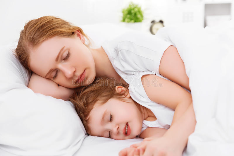 Madre felice e bambino della famiglia che dormono a letto fotografia stock libera da diritti