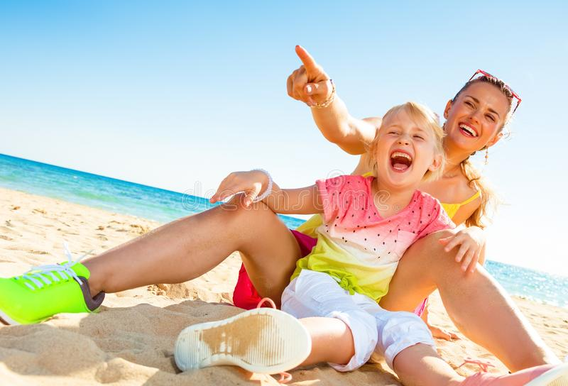 Madre felice e bambino moderni sulla spiaggia che indicano a qualcosa fotografia stock libera da diritti