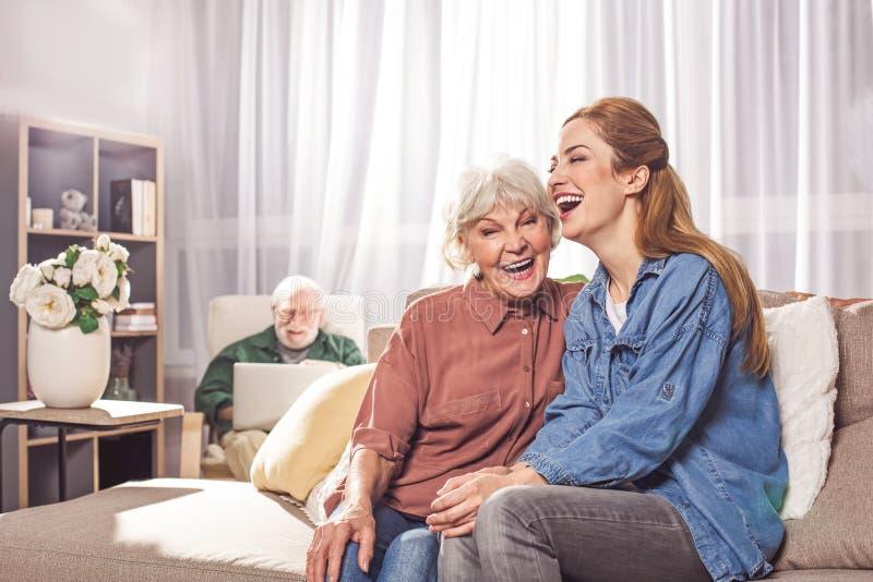 Madre felice e figlia anziane che si siedono sul sofà fotografie stock libere da diritti