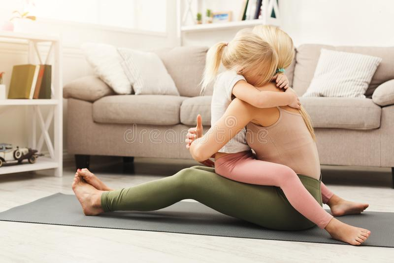 Madre felice e figlia che abbracciano mentre classe domestica di yoga fotografia stock libera da diritti