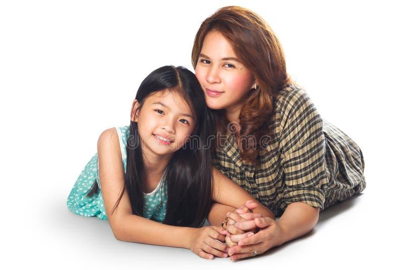 Madre felice e figlia che mettono sul pavimento fotografia stock