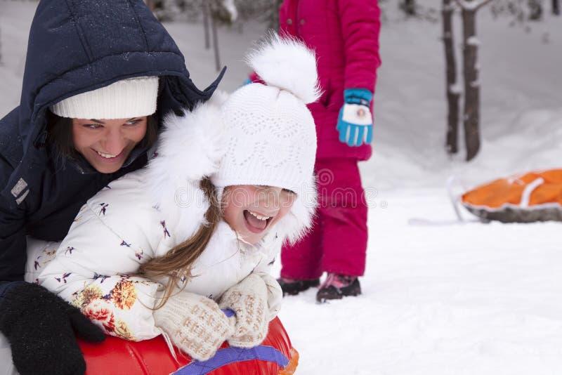 Madre felice e figlia che ridono e che rotolano con la collina della neve fotografia stock