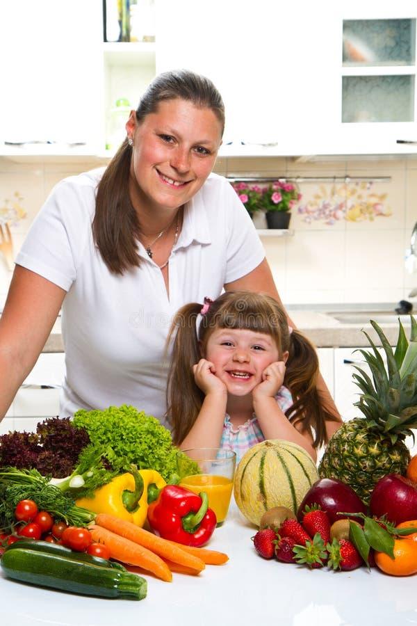Madre felice e figlia che sorridono nella cucina fotografia stock libera da diritti