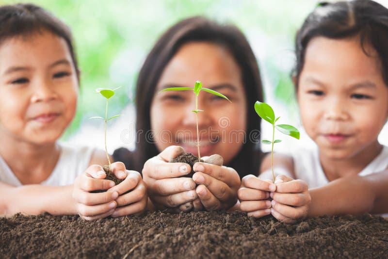 Madre felice e figlia della famiglia che tengono giovane albero immagini stock libere da diritti