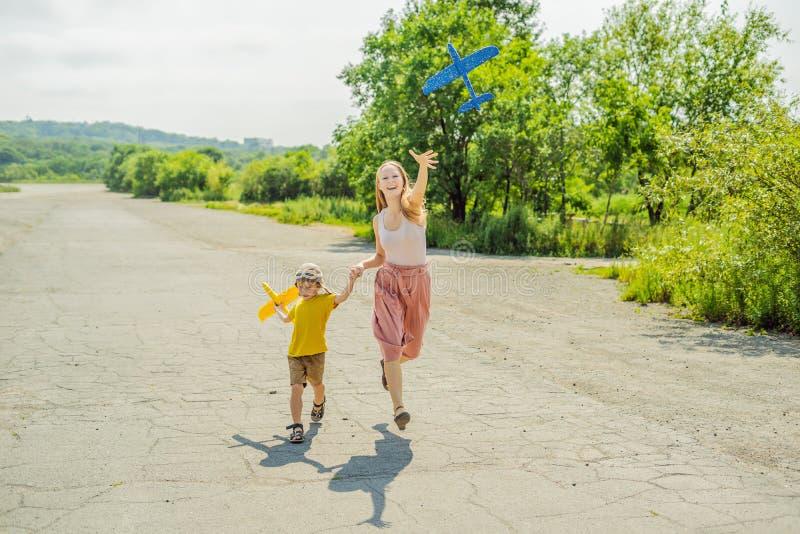 Madre felice e figlio che giocano con l'aeroplano del giocattolo contro il vecchio fondo della pista Viaggiando con il concetto d immagini stock libere da diritti