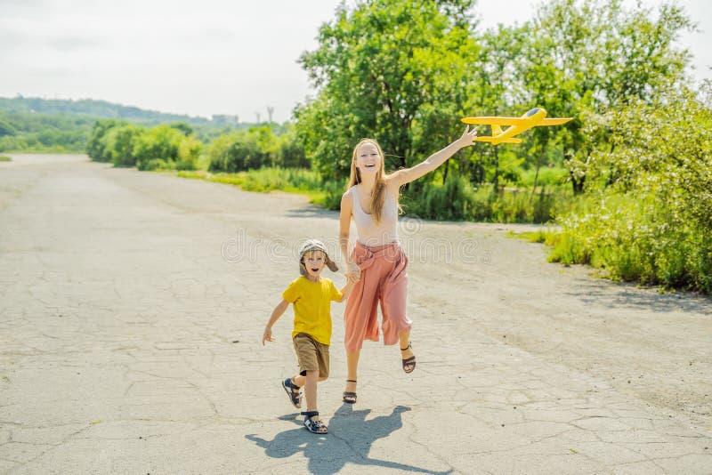 Madre felice e figlio che giocano con l'aeroplano del giocattolo contro il vecchio fondo della pista Viaggiando con il concetto d immagini stock