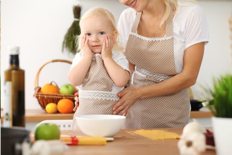 Madre felice e piccola figlia che cucinano nella cucina Spendendo tempo tutto insieme, concetto di divertimento della famiglia fotografia stock libera da diritti
