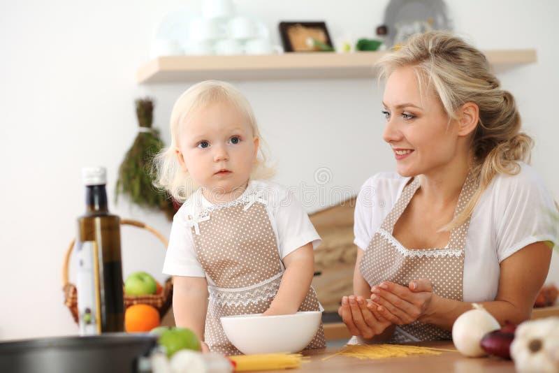 Madre felice e piccola figlia che cucinano nella cucina Spendendo tempo tutto insieme, concetto di divertimento della famiglia fotografie stock libere da diritti