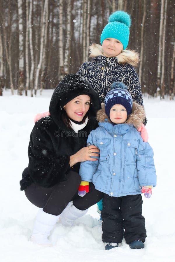 Madre feliz con el hijo, hija en día de invierno imagenes de archivo