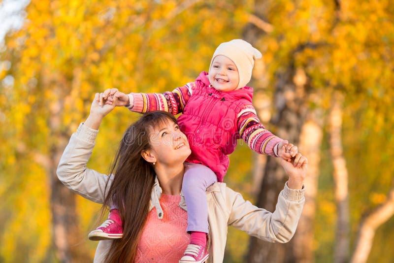 Madre feliz con la muchacha del niño que camina al aire libre en el otoño imagen de archivo