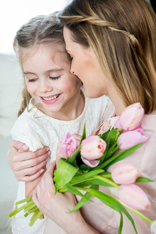 Madre feliz con los tulipanes que abrazan a la hija sonriente, concepto del día del ` s de la madre imágenes de archivo libres de regalías