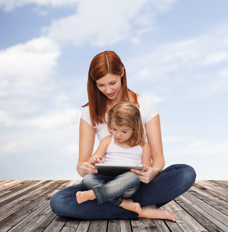 Madre feliz con PC de la niña y de la tableta fotografía de archivo libre de regalías