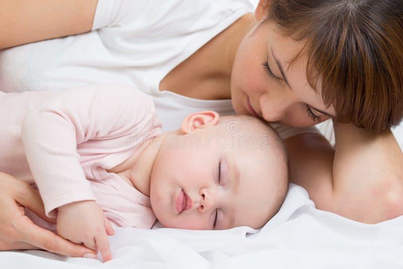 Madre feliz con su hija durmiente del bebé foto de archivo libre de regalías