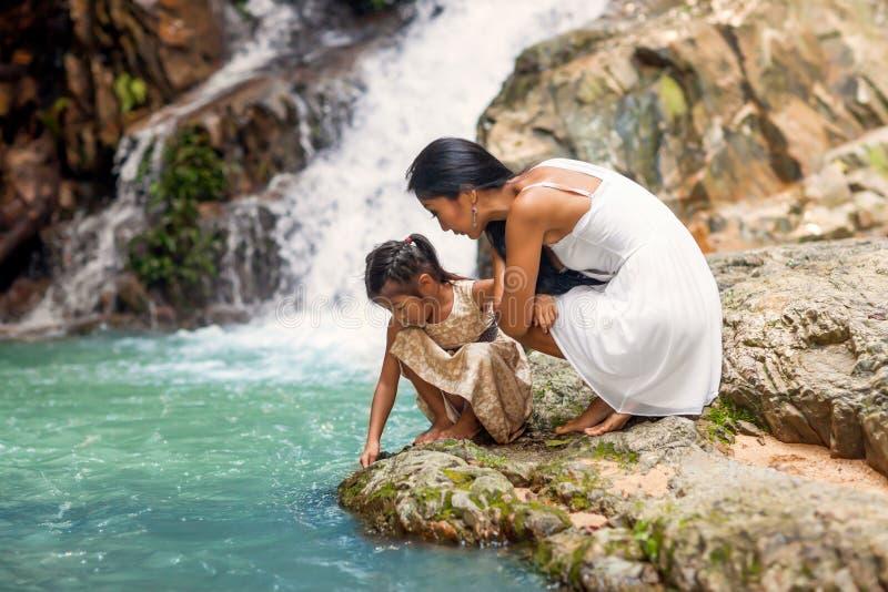 Madre feliz con su hija en las zonas tropicales cerca de la cascada imagenes de archivo