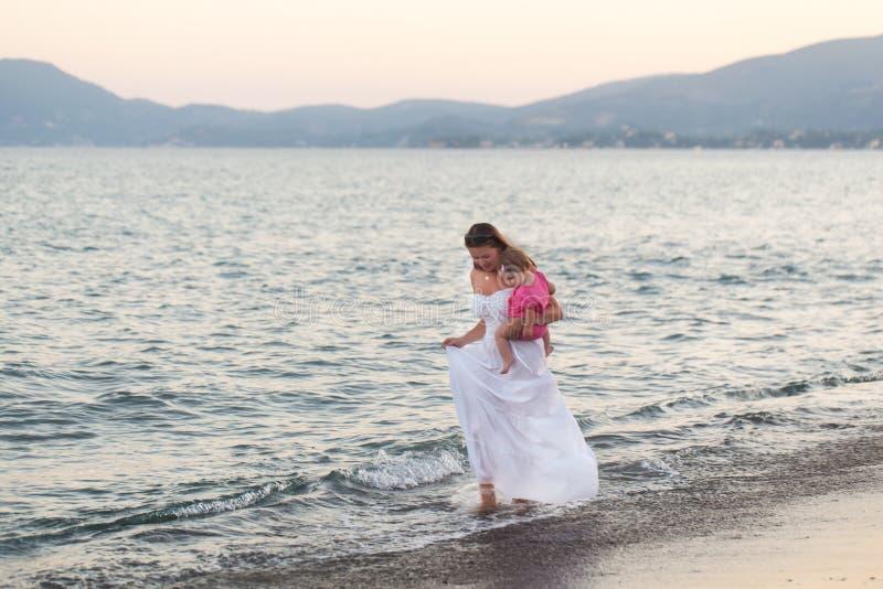 Madre feliz con una pequeña muchacha que camina en una playa foto de archivo