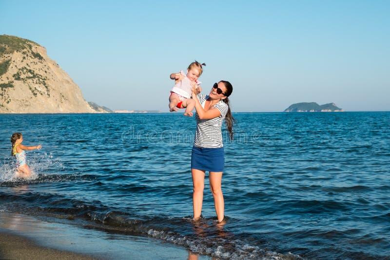 Madre feliz con una pequeña muchacha que camina en una playa foto de archivo libre de regalías