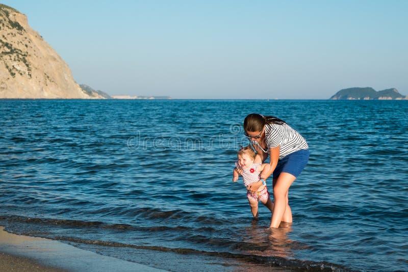 Madre feliz con una pequeña muchacha que camina en una playa fotos de archivo