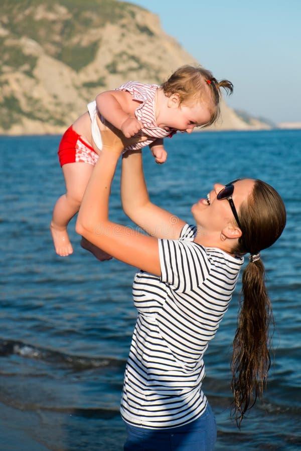 Madre feliz con una pequeña muchacha que camina en una playa fotografía de archivo