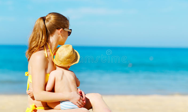Madre feliz de la familia con el hijo del bebé en la playa en verano imagen de archivo libre de regalías