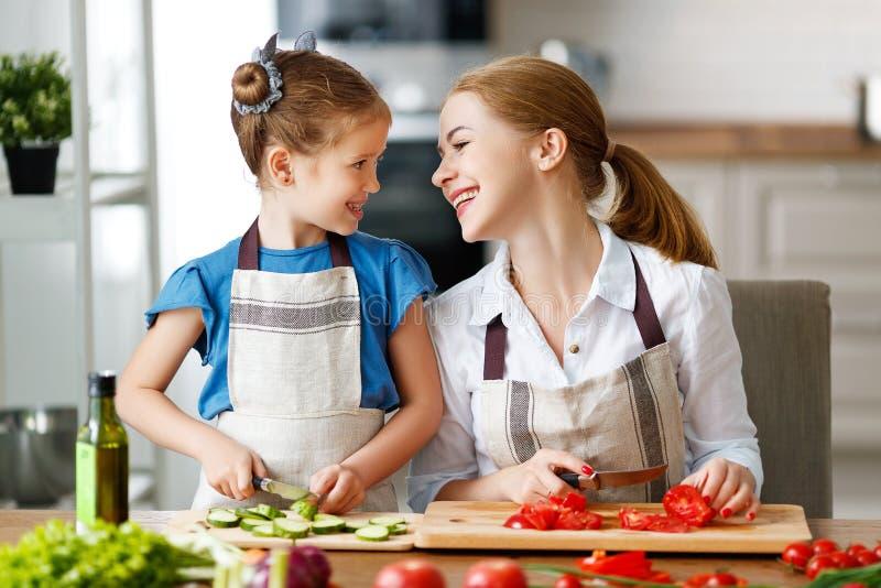 Madre feliz de la familia con la muchacha del ni?o que prepara la ensalada vegetal foto de archivo libre de regalías