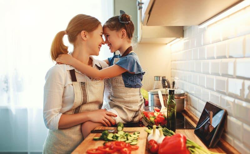 Madre feliz de la familia con la muchacha del ni?o que prepara la ensalada vegetal fotografía de archivo libre de regalías