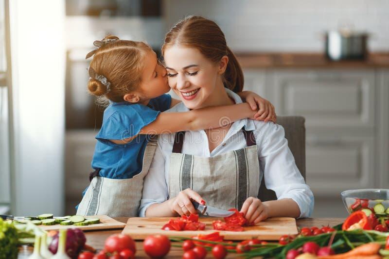 Madre feliz de la familia con la muchacha del ni?o que prepara la ensalada vegetal imagen de archivo libre de regalías
