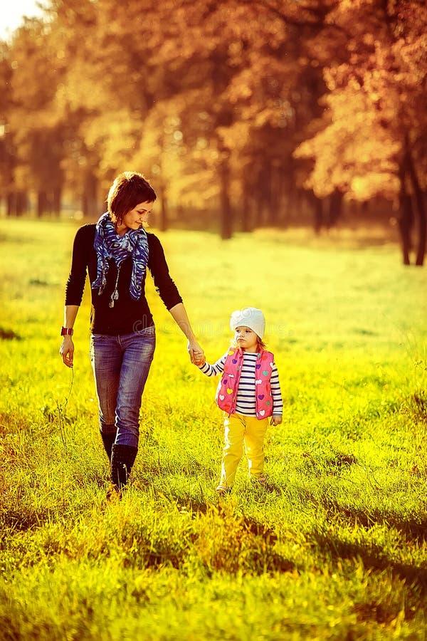 Madre feliz de la familia e hija del niño pequeña que camina el otoño imágenes de archivo libres de regalías