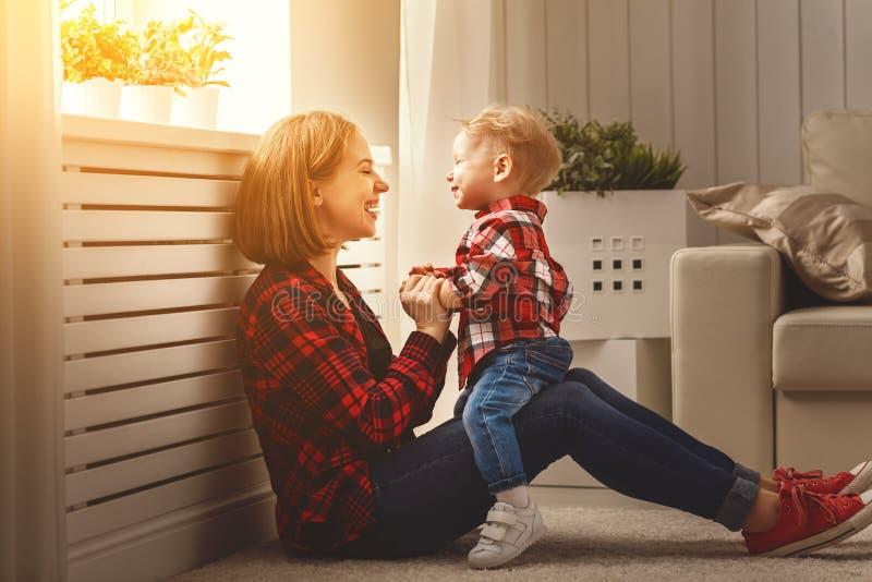 Madre feliz de la familia e hijo del bebé que abraza, jugando y riendo fotografía de archivo