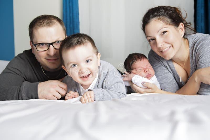 Madre feliz de la familia, padre y dos niños en casa en cama foto de archivo