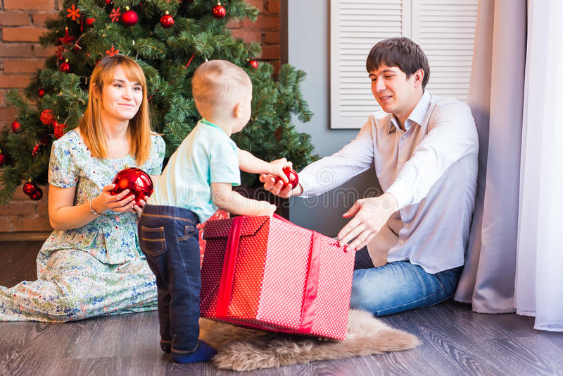 Madre feliz de la familia, padre y niño del bebé pequeño que juega en el invierno para los días de fiesta de la Navidad fotografía de archivo libre de regalías