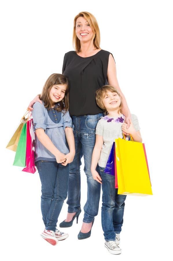 Madre feliz de las compras y sonrisa de las hijas foto de archivo libre de regalías