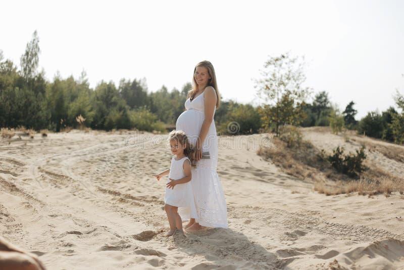 Madre feliz e hija embarazadas que se relajan en la playa imagen de archivo