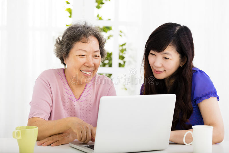 Madre feliz e hija mayores que aprenden el ordenador portátil imagen de archivo