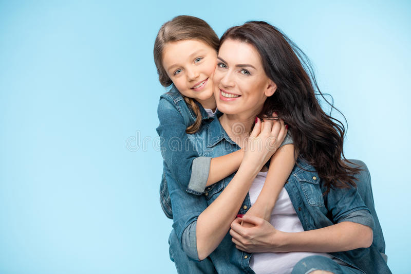 Madre feliz e hija que abrazan en estudio en azul foto de archivo libre de regalías
