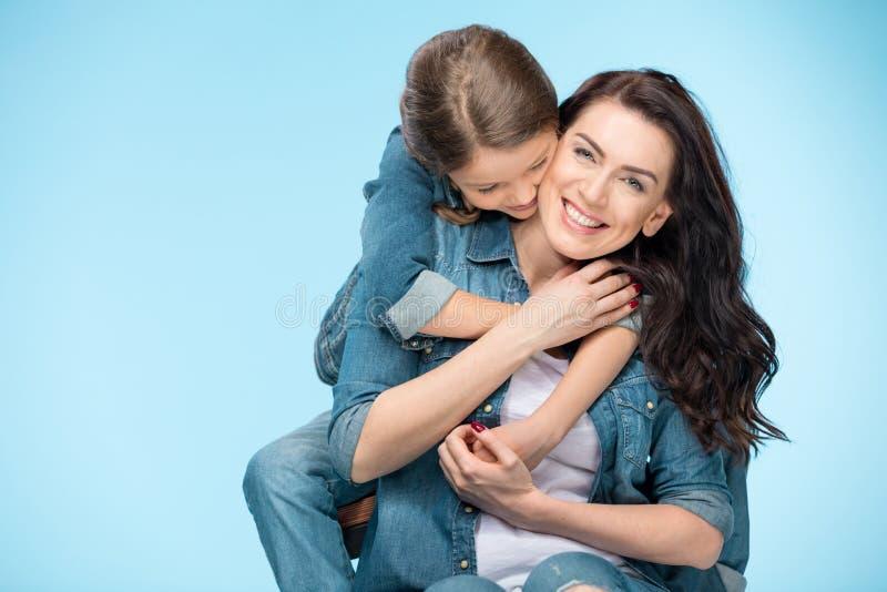 Madre feliz e hija que abrazan en estudio en azul fotografía de archivo libre de regalías