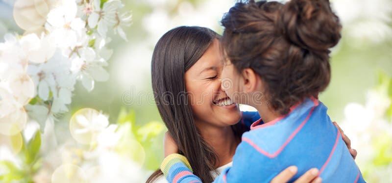 Madre feliz e hija que abrazan y que se besan imagen de archivo libre de regalías