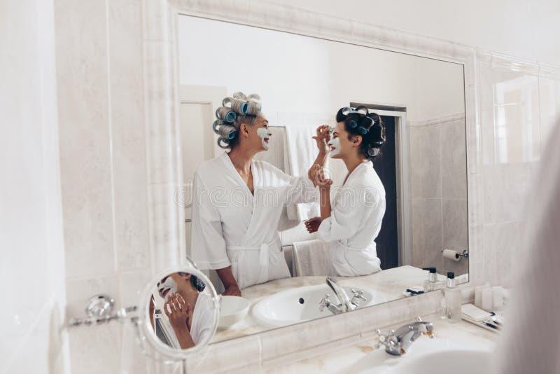 Madre feliz e hija que aplican la crema de cara que se coloca en los vagos imagen de archivo