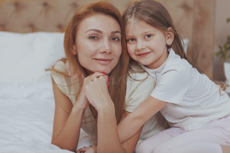 Madre feliz e hija que descansan en casa junto imagen de archivo