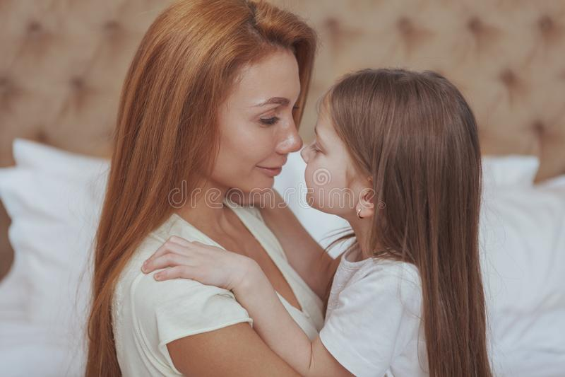 Madre feliz e hija que descansan en casa junto foto de archivo