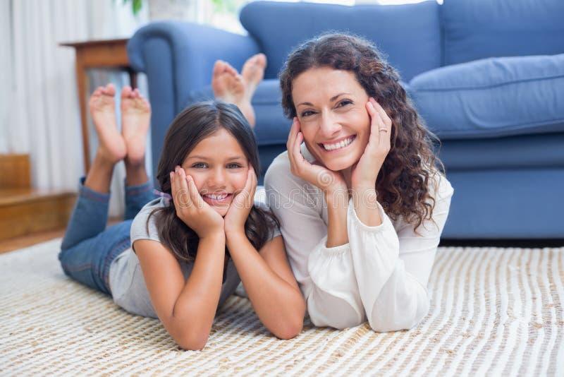 Madre feliz e hija que mienten en el suelo fotos de archivo