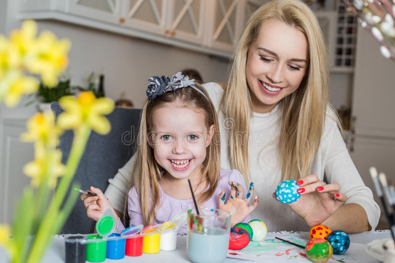 Madre feliz e hija que pintan los huevos de Pascua en la sala de estar fotos de archivo