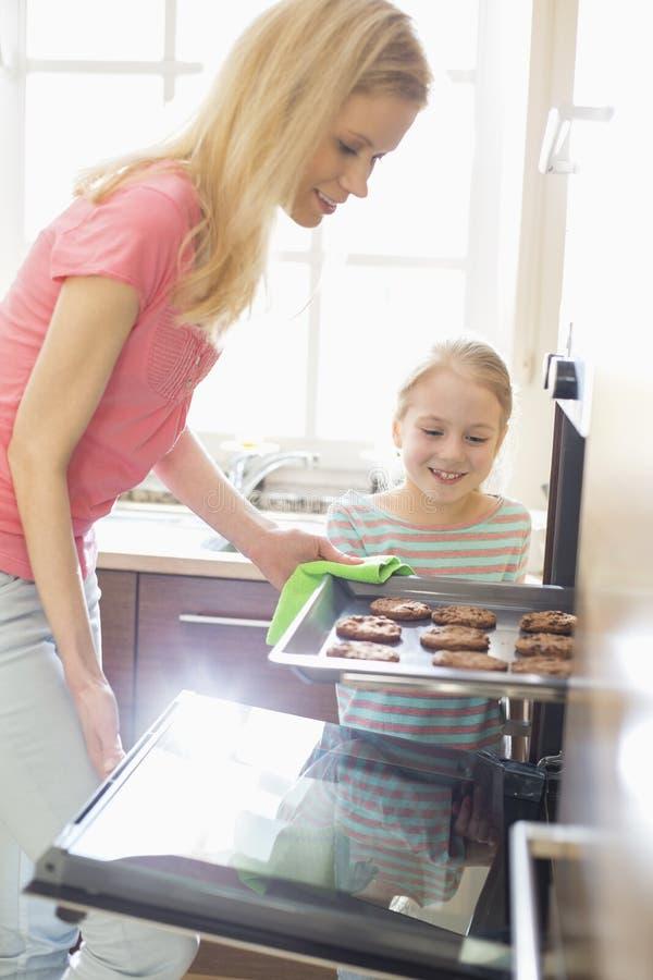 Madre feliz e hija que quitan la bandeja de la galleta del horno en casa fotografía de archivo libre de regalías