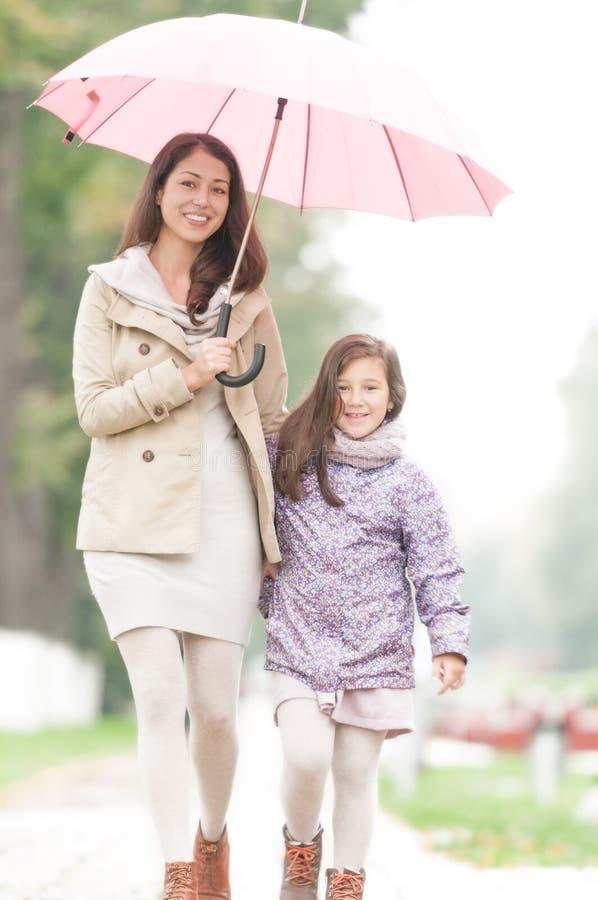 Madre feliz e hija que recorren en parque. foto de archivo