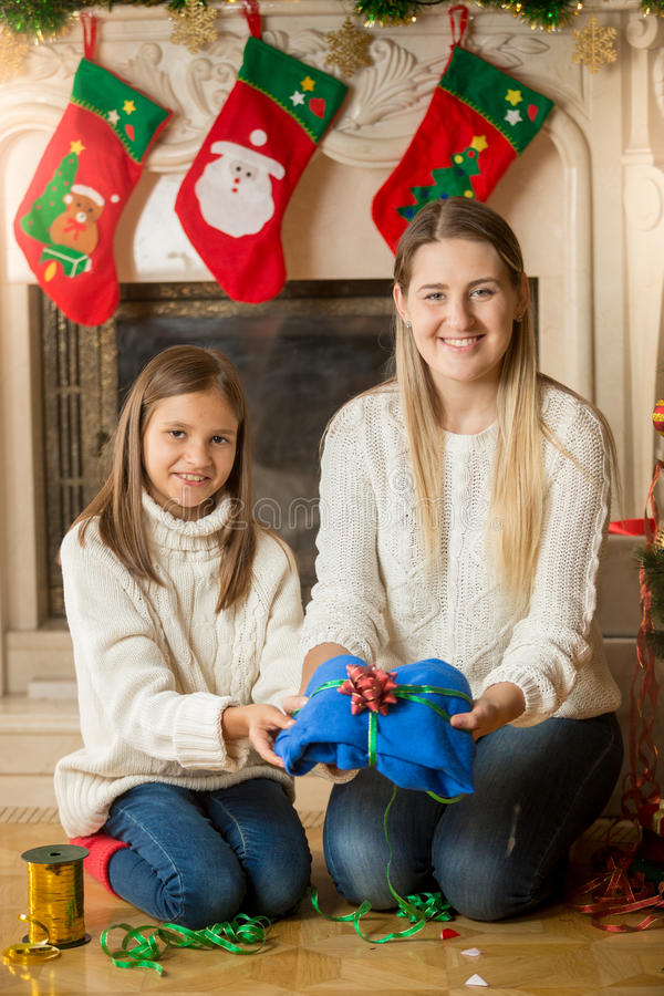 Madre feliz e hija que se sientan en piso en la chimenea y el paquete imagen de archivo libre de regalías