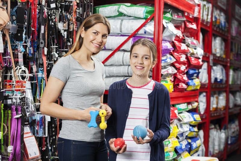 Madre feliz e hija que sostienen los juguetes en tienda del animal doméstico imágenes de archivo libres de regalías